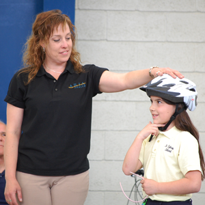 Child gets her helmet fitted at Bike to School Day event