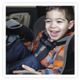 A smiling toddler safely buckled up in his car seat.