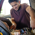 Father putting infant into car seat