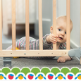 A baby pulling on a safety gate.