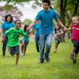 Kids run in a field along with their camp counselor.
