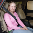 A teen safety sits in a car with their seat belt on securely.