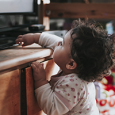 toddler reaching on top of media center to tv