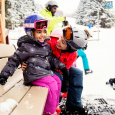 little girl getting ready to ski with her mom and family with the proper equipment