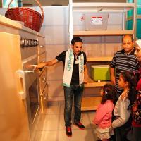Safe Kids staff demonstrates an oversize model kitchen
