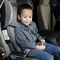 A young boy seating in his booster seat.