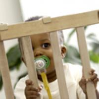 Toddler behind gate to keep her away from poisoning dangers