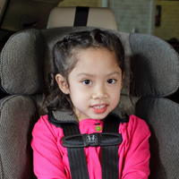 A toddler strapped in their car seat.