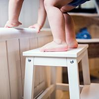 A toddler climbs a stool.