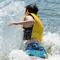A teenage boy dives into the open wearing a life jacket.