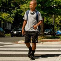 A teen crossing the street.
