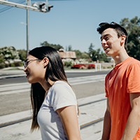 Two teens look out towards a railroad track.