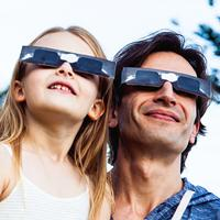 A father and daughter look up to the sky as they wear protective shade to protect their eyes from the sun.