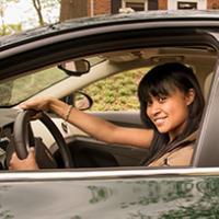 A teenage girl seat behind the steering wheel.