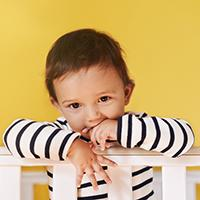 Toddler on railing of crib