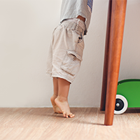 child reaching up on to a table on tip-toes
