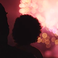 parent and child watch fireworks display from a distance
