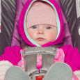 baby in rear-facing car seat with coat