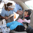 A car seat safety technician inspects a child in their car seat.