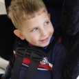 A smiling child buckled into his car seat.