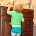 Toddler reaching up to bathroom counter.