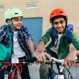 Two kids pose happily on their bikes with colorful helmets.