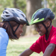 A mother and son smile at each other while wearing bike helmets.