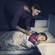little girl sleeping in bed while mom tucks her in
