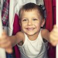 A young boy looking through his closet.