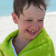 A young boy drying off after the pool.