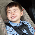 A child properly strapped into a car seat