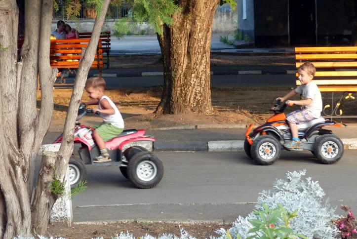 Traffic Park - Two little boys riding motorized cars with no protective gear at a traffic park for children.