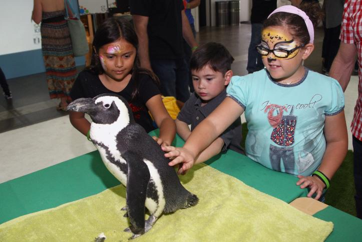 Kids interact with a penguin at Safe Kids Day 2016