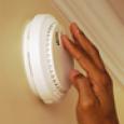 A hand reaches to check a smoke alarm.