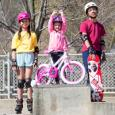 Three children pose for a photo as wear helmets and protective gear for wheeled sports.
