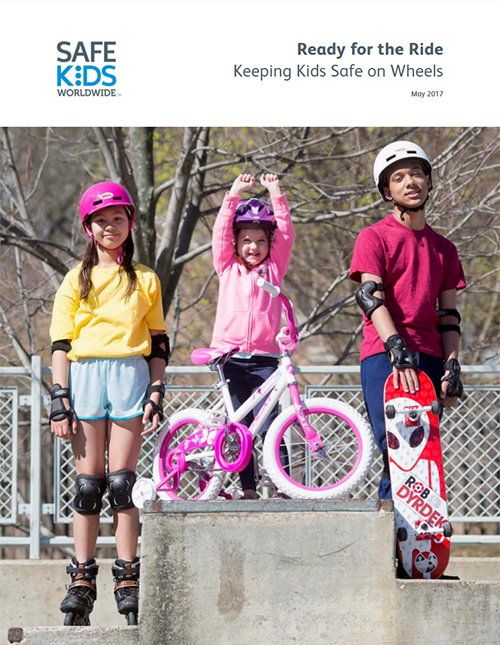 Three children standing triumphantly with their biking gear.